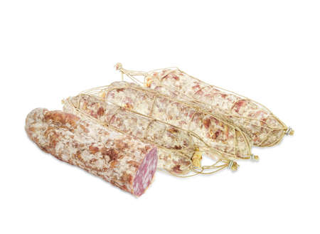 dry sausage: Several whole italian salami, tied with twine and one cut salami on a light background
