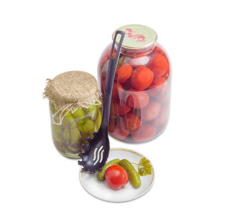 slotted: Two pickled cucumbers and one pickled tomato on a saucer, two various glass jars with pickled cucumbers and tomatoes and black plastic slotted spoon on a light background