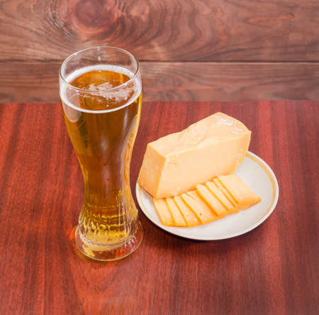brasserie: Beer glass with lager beer, one piece and several thin slices of hard cheese on saucer on wooden table against the backdrop of dark wooden planks