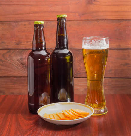 beerhouse: Glass of lager beer, two bottles of beer and several slices of cheese on saucer on wooden table against the backdrop of dark wooden planks