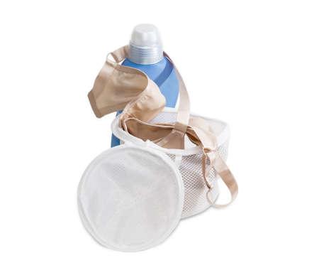 lavadora con ropa: bolsa de lavander�a especial para el lavado de los sujetadores en la lavadora contra el fondo azul botella de pl�stico de un detergente sobre un fondo claro
