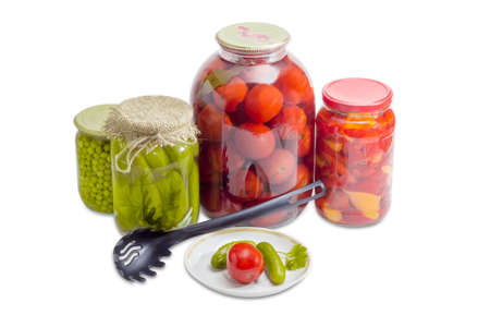slotted: Two pickled cucumbers and one pickled tomato on a saucer, pickled cucumbers, tomatoes, bell pepper and green peas in glass jars and black plastic slotted spoon on a light background Stock Photo
