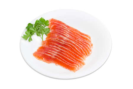 sprig: Sliced fillet of salted rainbow trout and a sprig of parsley on a white dish on a light background