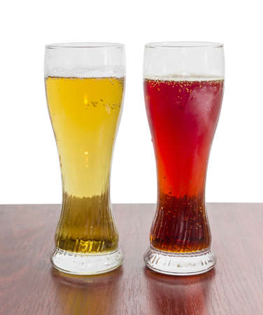 brasserie: Two beer glasses with lager beer and dark beer on a wooden table on a light background