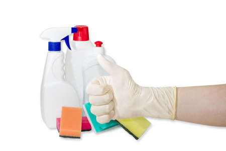 dish washing gloves: Hand gesture in household rubber glove thumb up against the backdrop of synthetic cleaning sponge and cleaning agents on a light background Stock Photo