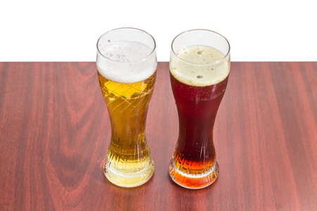 porter house: Two beer glasses with lager beer and dark beer on a wooden table on a light background