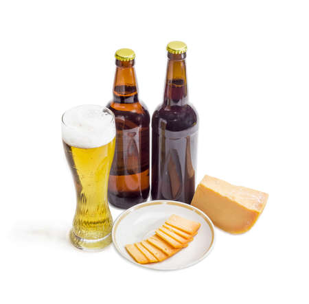 hard cheese: Beer glass with lager beer, two bottles beer, one piece and several thin slices of hard cheese on saucer on a light background