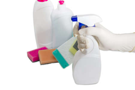 spray bottle: Hand in household rubber glove with spray bottle of cleaning agent on the background of several synthetic cleaning sponges and bottles of cleaning agent