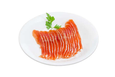 rainbow trout: Sliced fillet of salted rainbow trout and a sprig of parsley on a white dish on a light background