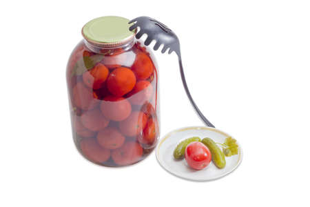 slotted: Glass jar with canned tomatoes, two canned cucumbers and one canned tomato on a saucer and black plastic slotted spoon on a light background Stock Photo