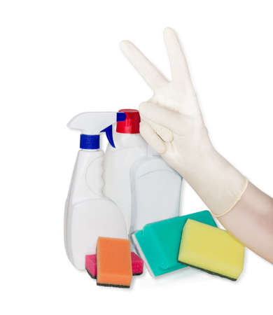 dish washing gloves: Victory symbol hand gesture in household rubber glove against the backdrop of synthetic cleaning sponge and cleaning agents on a light background Stock Photo