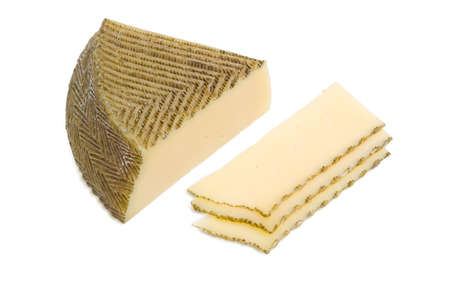 kitchen spanish: Piece and several slices of semi-hard Spanish cheese with dark coating manufactured from mixtures of cow and sheep milk on a light background Stock Photo