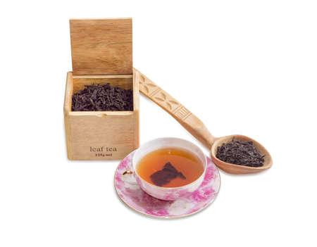 tazza di th�: piattino rosa e tazza di t� nero, Grande foglia di t� nero in una scatola di legno e cucchiaio di legno su uno sfondo chiaro