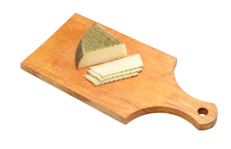 kitchen spanish: Piece and several slices of semi-hard Spanish cheese with dark coating manufactured from mixtures of cow and sheep milk on a wooden kitchen cutting board on a light background Stock Photo