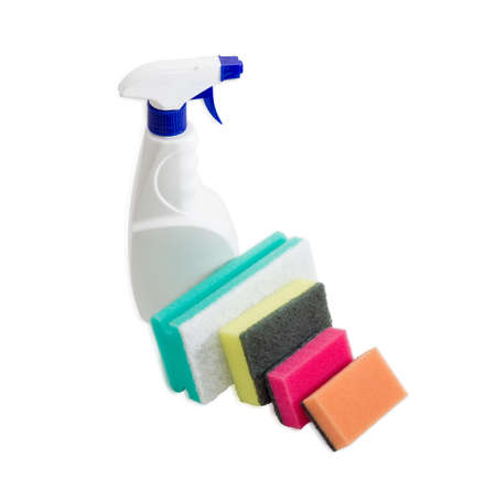 impervious: Several synthetic cleaning sponges with layer for more intense scrubbing different colors and sizes and plastic spray bottle of cleaning agent on a light background