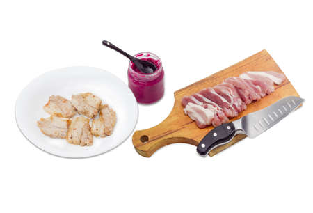 horseradish sauce: Several slices of fried pork on white dish,  small glass jar of horseradish sauce,  sliced uncooked pork belly and kitchen knife on a wooden cutting board on a light background Stock Photo