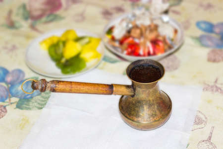 long handled: Old copper coffee pot with long wooden handle with freshly brewed Turkish coffee on a table Stock Photo