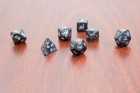 roleplaying: Set of specialized polyhedral dice with numbers used in role-playing games on a wooden surface