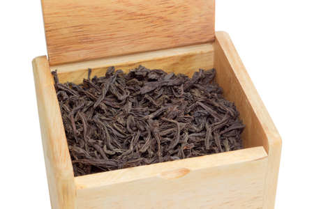 tea party: Dried large tea leaves of black tea in a wooden box on a light background closeup