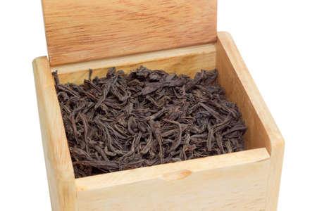 Getrocknete große Teeblätter von schwarzem Tee in einer Holzkiste auf einem hellen Hintergrund Nahaufnahme