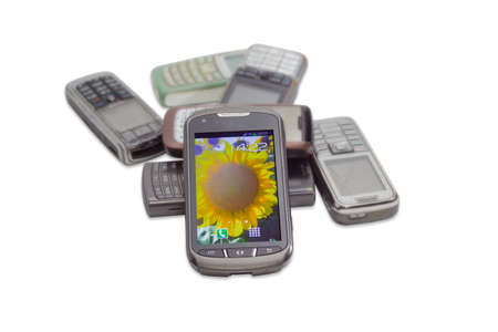 the outdated: Modern smartphone with touchscreen on the background of several old shabby outdated mobile phones on a light background