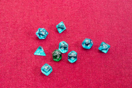 specialized: Set of blue and green specialized polyhedral dice with numbers used in role-playing games on a table with red cloth