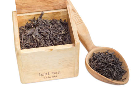 party food: Large leaf of black tea in a wooden box and wooden spoon on a light background closeup