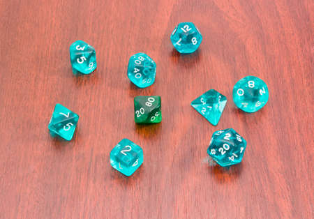specialized: Set of blue and green specialized polyhedral dice with numbers used in role-playing games on a wooden surface