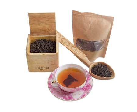 party food: Saucer and cup of black tea, different varieties of tea leaves in paper bag, wooden box and wooden spoon on a light background Stock Photo