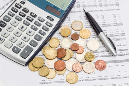 cents: Several euro coins from 1 cents to 2 euro scattered on the printed table with data, pen and fragment of a calculator