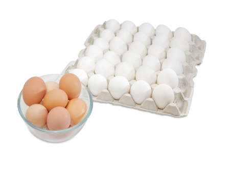 chicken cage: Fresh brown free-range eggs in a glass bowl and white chicken eggs in an egg tray from commercial factory farming on a light background Stock Photo