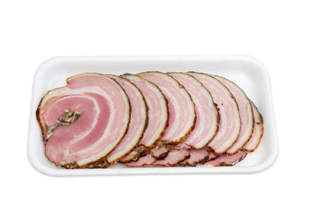 muscle belly: Sliced roll of a baked pork belly with layers of muscle and fats on a plastic tray on a light background Stock Photo