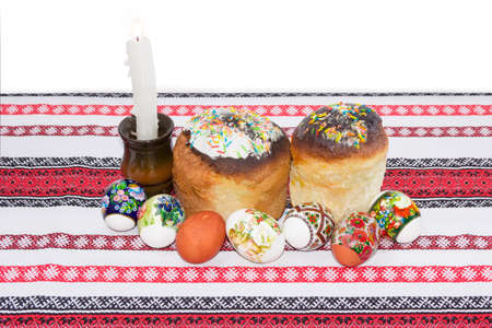 easter candle is burning: Two Easter cake decorated with white icing and colorful sugar decors, several Easter eggs with a various decorating and burning candle on a tablecloth with ornament on a light background
