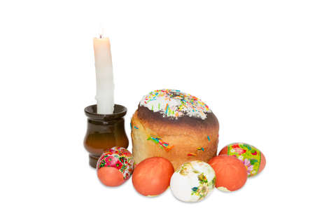 easter candle is burning: Easter cake decorated with white icing, colorful sugar decors, several Easter eggs with a various decorating and burning candle on a light background Stock Photo