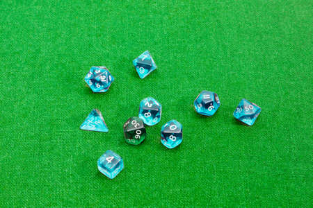 specialized: Set of blue and green specialized polyhedral dice with numbers used in role-playing games on a table with green cloth
