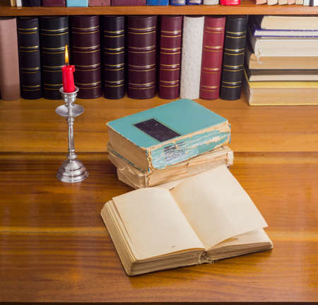 bibliophile: Open old book, stack of other old shabby books and a burning candle in candlestick on a wooden table against the background of shelf with books