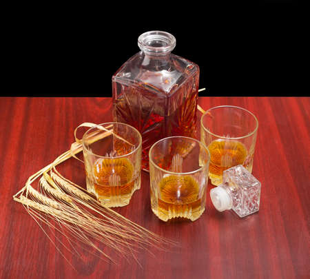 decanter: Decanter and three glasses with whiskey, stopper from the decanter and several barley spikes on a wooden table on a dark background