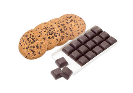 semisweet: Several chocolate chip cookie and square pieces of dark chocolate in the opened packing on a light background