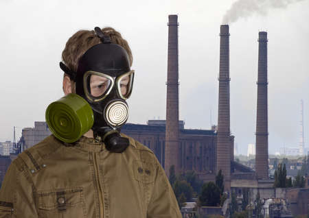 thermal pollution: Man in a rubber gas mask against the backdrop of a thermal power station with several brick flue-gas stacks Stock Photo