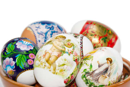 paschal: Several Easter eggs with a different patterns and pictures of an angels in a ceramic bowl on a light background closeup