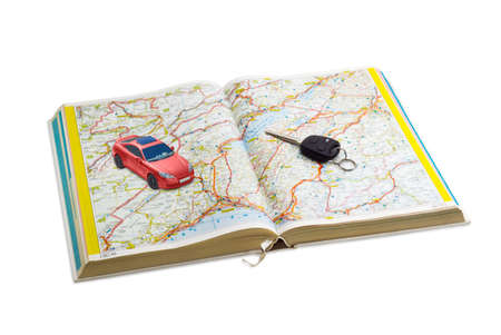 hardcovers: Car key and red toy car on the open road atlas on a light background Stock Photo