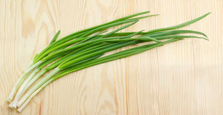 green onion: Bunch of a fresh green onion on a light wooden surface