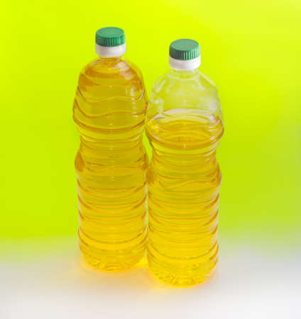 unrefined: One full and one partially filled plastic bottle of unrefined sunflower oil on an yellow background