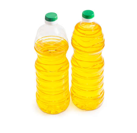 unrefined: One full and one partially filled plastic bottle of unrefined sunflower oil on a light background