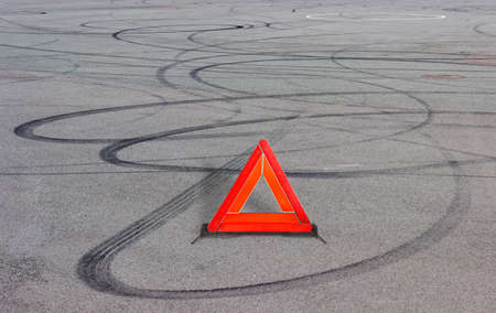 skidding: Warning triangle fixed on road and curve dark rubber tires tracks of braking and skidding on a gray asphalt surface Stock Photo