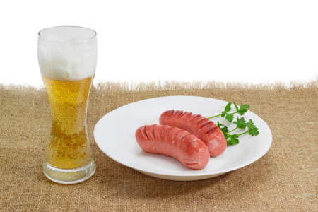 tipple: Two fried thick frankfurters and a sprig of parsley on a white dish and glass of a lager beer on a surface by sackcloth on a light background