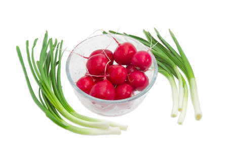 spring green: Fresh washed red radish in transparent glass bowl against the two bunches of green onion on a light background