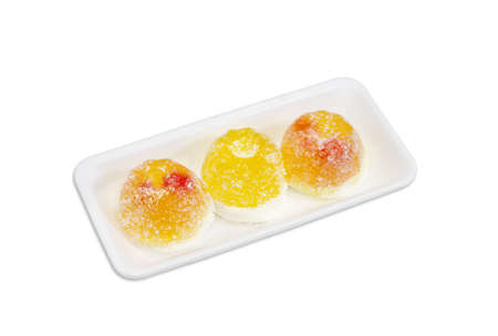 fruit jelly: Three yellow fruit jelly candies gelatin based with jam inside and coated in granulated sugar in a small plastic tray on a light background Stock Photo