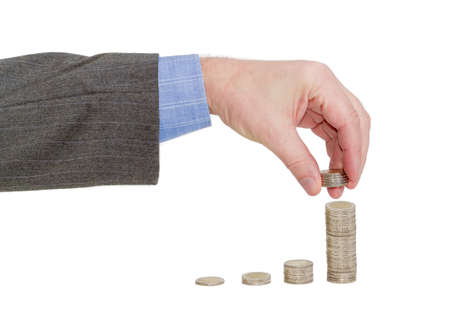 adds: Male hand adds a several coins to the last column of the diagram consisting of columns of euro coins on a light background Stock Photo