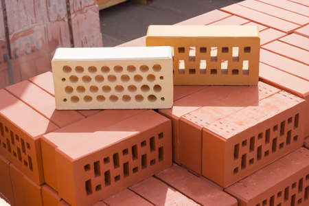 Two common perforated bricks of different colors with round and rectangular holes on a pallet with bricks on the background other pallets with bricks Standard-Bild